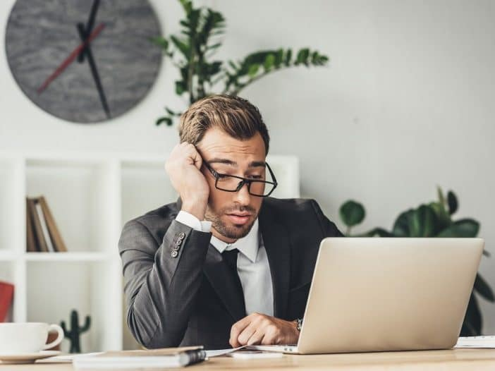 Exhausted worker staring at his laptop