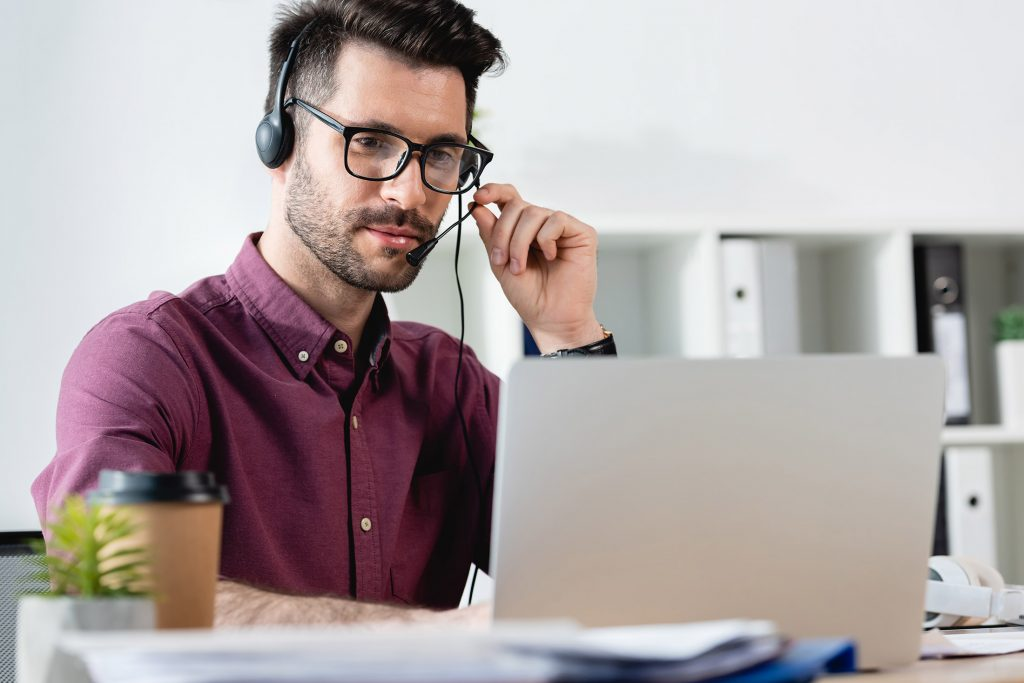 Professional man using voip business phone at desk